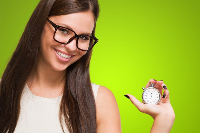How long it takes for Invisalign to work? Young woman holds stopwatch for teeth straightening.